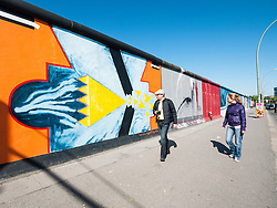 Tourists look at paintings on wall at East Side Gallery at former Berlin Wall in Friedrichshain/Kreuzberg in Berlin Germany