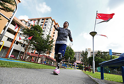 Aishah does a brisk walk around the park in front of her home apartment block in Singapore, 21 July 2014.  Aishah starts training to get back into shooting which includes training three times a week at an air rifle club and doing exercises in the park in front of her apartment block.