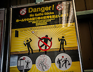 """A sign bans the use of selfie sticks on a train platform in Kyoto in Japanese, English, Chiness and Korean.  Recently selfie sticks were banned by West Japan Railway Co. (JR West), which serves Kyoto.  """"The sticks annoy other commuters, JR West said.   Many tourism facilities because of the risk of electricution or even their use to make secret photos, like at onsen hot springs where genders, soaking without clothing, may only be protected from view by a low wall.  Inari Station, Kyoto, Japan."""