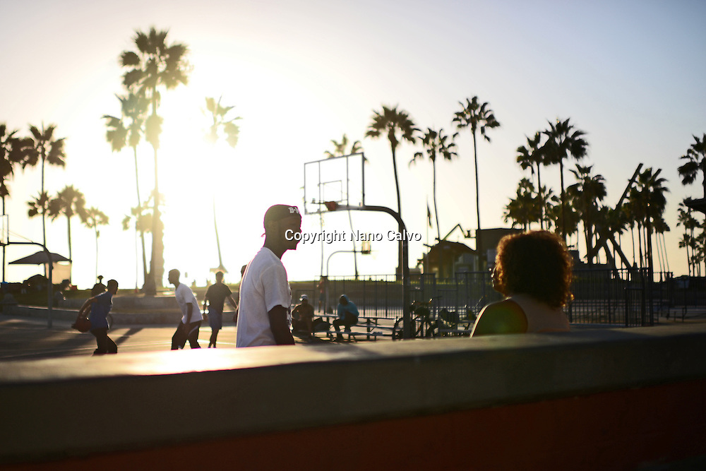 People and street basketball game at sunset in Venice Beach, California.