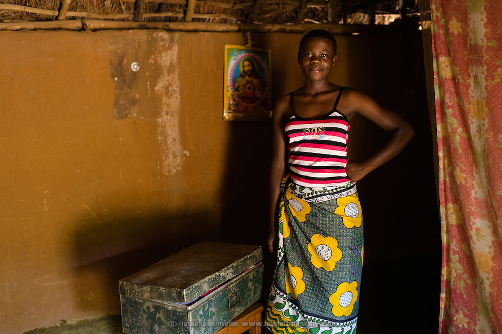 """Catherine Apoyo, pictured on 2 August 2014, keeps her Afripads in a metal trunk of her belongings at her home near Tororo, Uganda. She says, has been using Afripads for three months, and says of them """"It's very good. It's comfortable."""" Previously she would use rags when she had her period, and said, """"Sometimes blood would come out onto my skirt, or they can even fall down when you are walking."""" She would stay home from school at times, because she was not comfortable going out with the rags."""