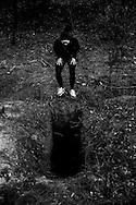 Cecília looking a hole on an abandoned backyard.