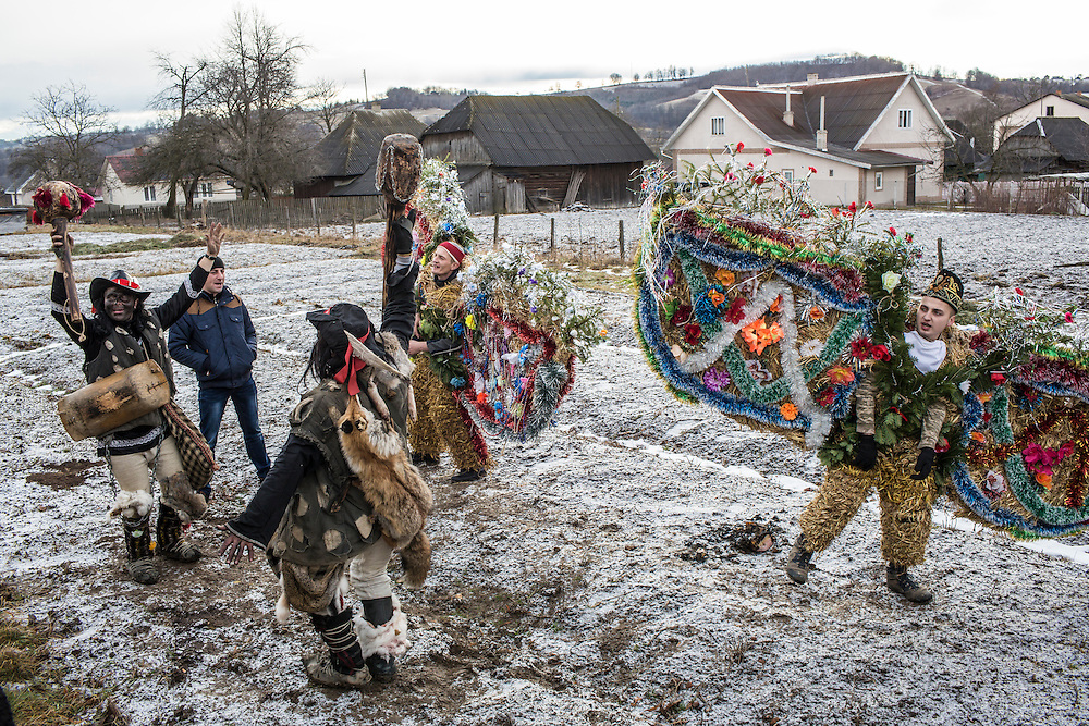 Petro Dragun, 18, right, and others in costume celebrate the Malanka Festival on Thursday, January 14, 2016 in Krasnoilsk, Ukraine. The annual celebrations, which consist of costumed villagers going in a group from house to house singing, playing music, and performing skits, began the previous sundown, went all night, and will last until evening.
