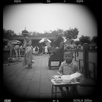 Asia, China, Beijing, Blurred black and white image of young boy eating lunch at photo studio set up in the Forbidden City