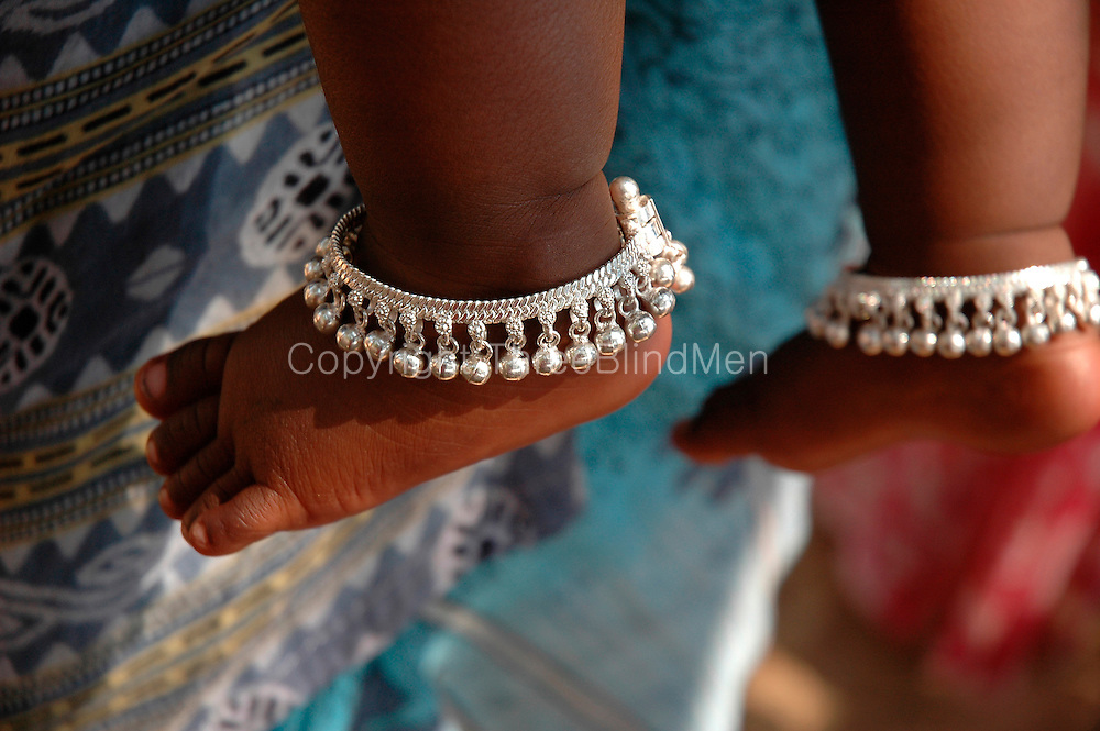 Baby with silver anklet.