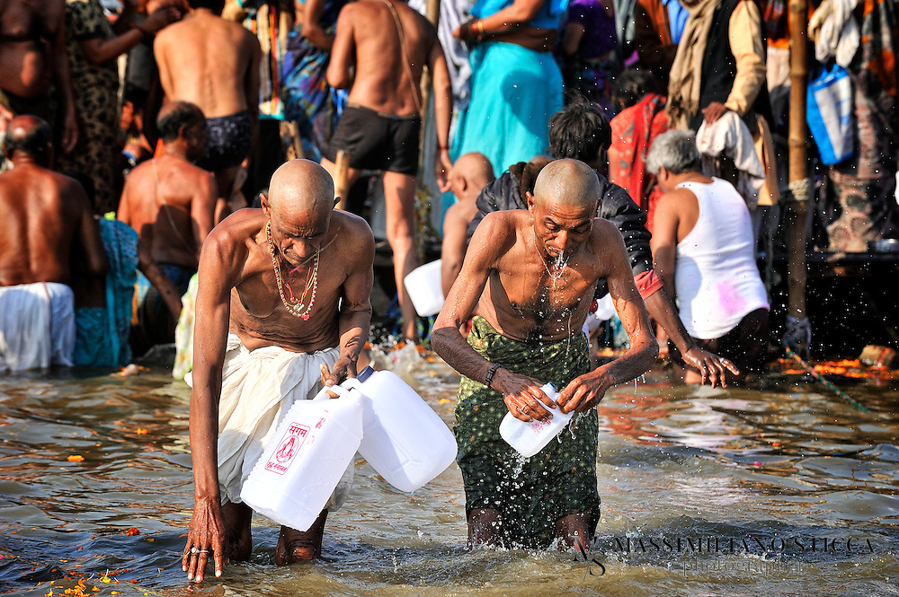 Pilgrim fill canisters with holy water from the Ganges..