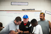 BEAUFORT, SC - JULY 14: Coach Ray Jones, center, uses the dry eraser board to motivate CJ Cummings, front right, during a work out at the Beaufort Middle School on July 14, 2014 in Beaufort, South Carolina. Cummings is competing at the Open Men's Nationals in July.  (Photo by Stephen B. Morton for The Washington Post)