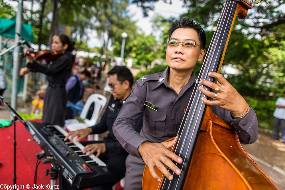 """15 JUNE 2014 - BANGKOK, THAILAND:  A Thai police jazz trio performs on a stage during a """"Return Happiness to Thais"""" party in Lumpini Park in Bangkok. The Thai military junta, formally called the National Council for Peace and Order (NCPO), is sponsoring a series of events throughout Thailand to restore """"Happiness to Thais."""" The events feature live music, dancing girls, military and police choirs, health screenings and free food.  PHOTO BY JACK KURTZ"""