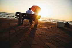 A couple sit at sunset on a bench facing the ocean, Colombo, Sri Lanka, Asia