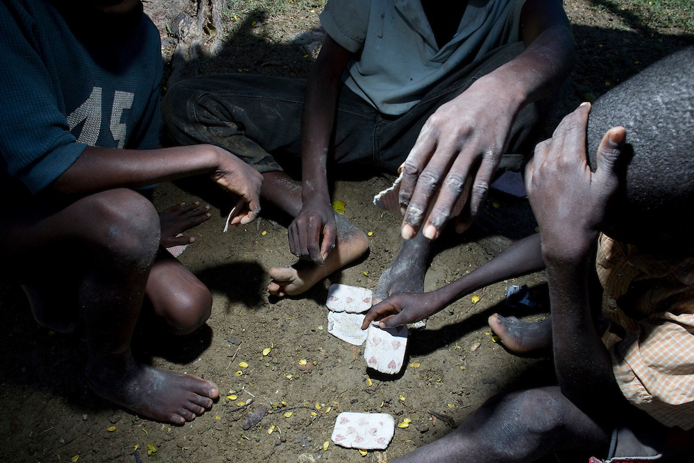 Boys play cards on the ground.