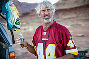 SHOT 10/16/16 6:12:15 PM - Paul Hobson of Steamboat Springs, Co. takes a swig of rum while camping at the Airport camp spot on the White Rim. The White Rim is a  mountain biking trip in Canyonlands National Park just outside of Moab, Utah. The White Rim Road is a 71.2-mile-long unpaved four-wheel drive road that traverses the top of the White Rim Sandstone formation below the Island in the Sky mesa of Canyonlands National Park in southern Utah in the United States. The road was constructed in the 1950s by the Atomic Energy Commission to provide access for individual prospectors intent on mining uranium deposits for use in nuclear weapons production during the Cold War. Four-wheel drive vehicles and mountain bikes are the most common modes of transport though horseback riding and hiking are also permitted.<br /> (Photo by Marc Piscotty / &copy; 2016)