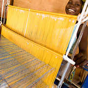 A woman uses traditional looms to weave textile at the Village Artisanal de Ouagadougou, a cooperative that employs dozens of artisans who work in different mediums, in Ouagadougou, Burkina Faso, on Monday November 3, 2008.