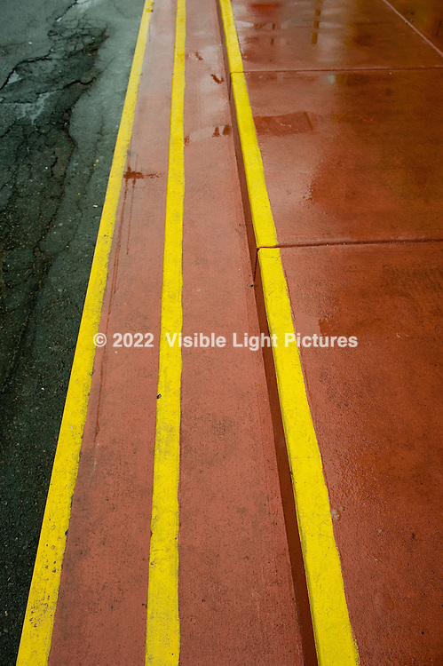Yellow stripes along steps on a wet street.