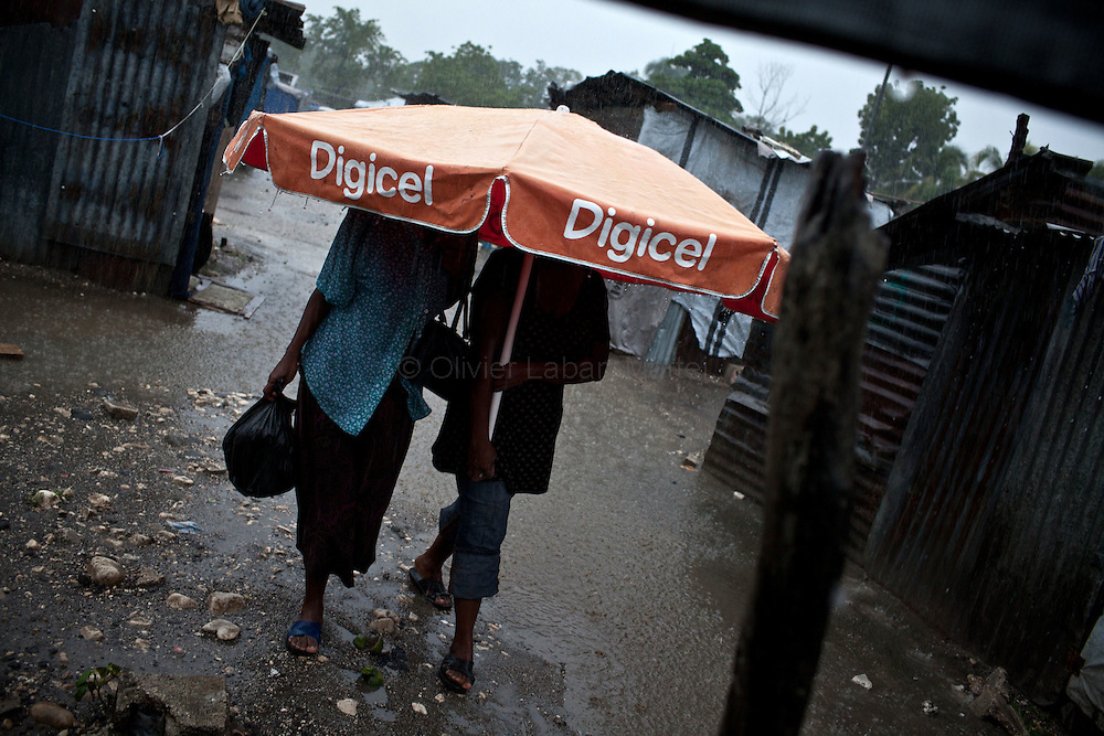 After hurricane Tomas went through Haiti, the city of Leogane has been totally flooded by the heavy rain and the overflow of the river Roullorne.///Two Haitian women leaving in a refugee camp in Leogane since the earthquake in January, shelter under a parasol during hurricane Tomas.