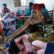 Sylivia Nalule sewing pads at the Afripads factory in the village of Kitengeesa in the Central Region of Uganda on 30 July 2014.<br /> <br /> Started by volunteers in 2009, Afripads manufactures reusable fibre sanitary pads made locally by community residents. Beginning with a single employee, the company now employs roughly 100 women and produces approximately 700 kits (consisting of pads, holders and a bag) each week. At USh 12,000 to 15,0000 (&pound;2.75 to &pound;3.40) for a kit that lasts approximately one year, Afripads offer a significant saving over disposables which may cost in excess of USh 42,000 (&pound;9.60) over the course of a year. And for the many girls and women who cannot afford disposables, they offer an affordable and more hygienic alternative to rags, cotton wool or toilet paper, all of which are frequently used. At schools where Afripads have been distributed, teachers report that absenteeism has dropped sharply as girls who previously did not have access to proper sanitary pads now no longer stay home when they have their periods.