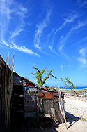 Wispy clouds over a house on the coral foreshore of Caletones near Gibara, Holguin, Cuba.