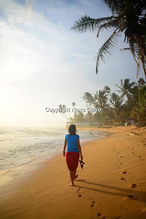 Young woman walking on Hikkaduwa beach at sunset, Sri Lanka
