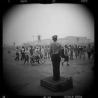 Asia, China, Beijing, Blurred black and white image of policeman standing guard at Gate of Heavenly Peace in the Forbidden City on summer afternoon