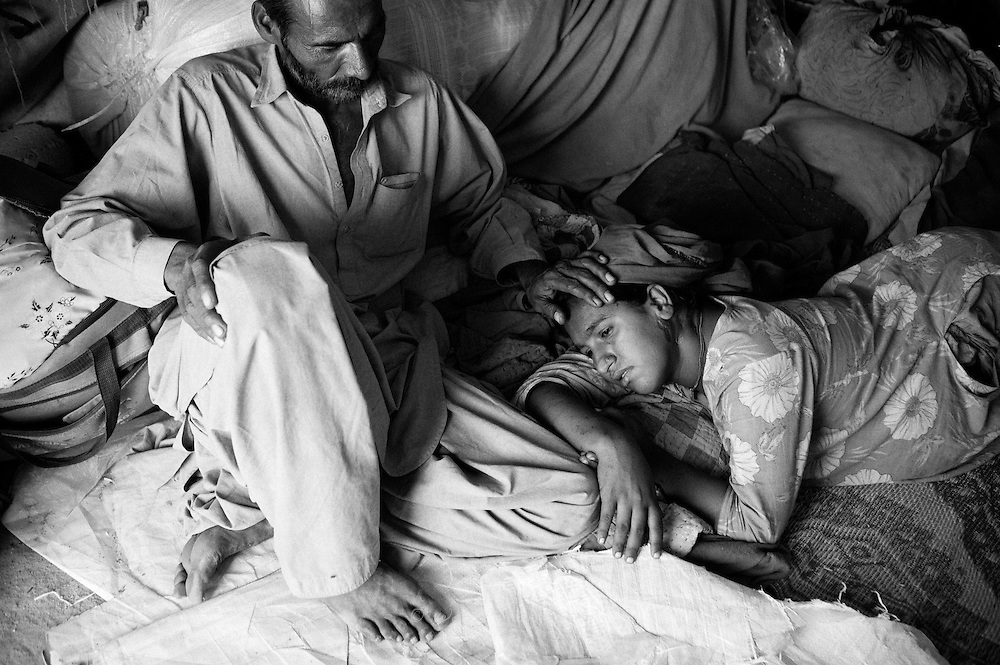 Mohammad Ali softly pads Hamida on her head who is counting down the final days, waiting to give birth to their 4th child. Karachi, Pakistan, 2010
