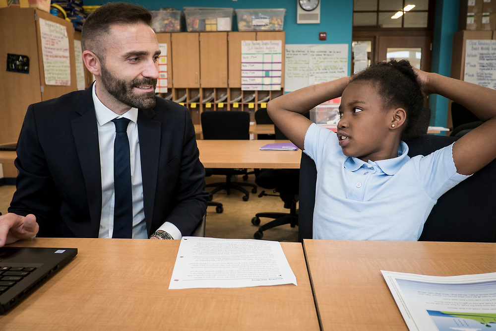 Eric Christopher, Leap ELA Instructional Coach at Turner Elementary School in Washington, D.C., tests a student's reading abilities and comprehension on Wednesday, May 4, 2017.