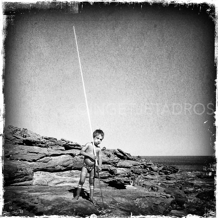 Equaylin, four year old, standing on the rocks while holding his spear which he uses to catch fish. The previous night Equaylin took part in a traditional dance, a corroboree in Middle Lagoon. He still wears the ochre<br />