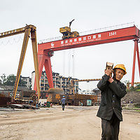 China, Chongqing, Workman carries heavy box at sprawling Chongqing Dongfeng Shipyard on autumn morning
