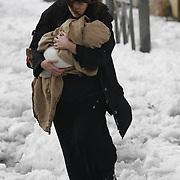 Israeli mother hold her baby during snow storm in Jerusalem. December 13, 2013.  Photo by Oren Nahshon