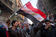 """Protestors wave an Egyptian flag stained with blood as they confront the Egyptian miliary during a moment of a cease fire between the protestors and Egyptian military. A crowd of tens of thousands filled Cairo's Tahrir Square Tuesday, answering the call for a million people to turn out and intensify pressure on Egypt's military leaders to hand over power to a civilian government. The ruling military council held crisis talks with political parties across the spectrum to try to defuse growing cries for a """"second revolution.""""(Photo by Heidi Levine/Sipa Press)."""