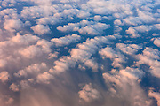 The north Atlantic Ocean is visible in breaks between bands of cumulus clouds in this aerial view captured between Greenland and Iceland. The tops of the clouds are turned red by the rising sun.