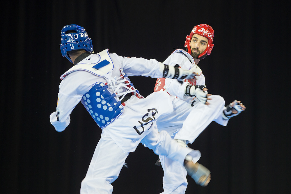 Maxine Potvin (R) of Canada and Terrence Jennings of the United States  trade kicks during their semifinal contest in the men's -68kg weight class of Taekwondo at the 2015 Pan American Games in Toronto, Canada, July 20,  2015.  AFP PHOTO/GEOFF ROBINS