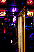 The exit sign to the dressing room is reflected in the mirrored walls at the world famous Mons Venus strip club in Tampa, Florida.