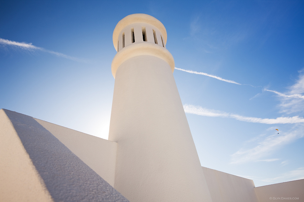 A hang glider flies past overhead, below vapour trails across a blue sky. A white chimney, characteristic of this part of the Algarve points skywards.