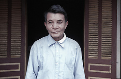 Portrait of an old vietnamese man posing in front of shelters. Nam Dinh province, Vietnam, Southeast Asia