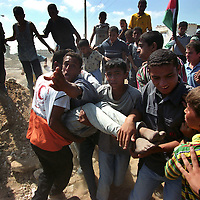Palestinian youths carry a boy that was wounded when Israeli forces open fire on the stone throwers in Dayr al Balah in the Gaza Strip. (Photo/Scott Dalton)