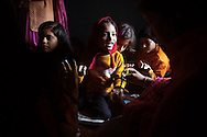 Akaancha Kumari, 8, center, points to the hand of bride Suman Kumari, left, as she and other young family members have their own hands decorated with henna in preparation for the wedding, to be held later in the day, at Suman's family home in Bakarour village, Bihar, India, December 9, 2011. Though Indian law strictly prohibits marriage before age eighteen, 69 percent of girls in rural Bihar are married by that age.