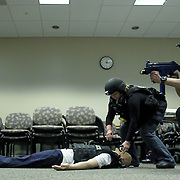 Master Sergeant Adam B. Ringle (RIGHT) and registered nurse Kelly Green-O'shaughnessy (CENTER) attaches a Tactical Tech Rescue Device to a life like mannequin during a secure and rescue scenario in the course of an Active Shooter workshop Sunday, Mar 16, 2014 Christina Hospital in Newark Delaware.
