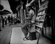 Sidelong glance from pirated DVD street vendor opposite the Maroon market.   Paramaribo, Suriname.  Young Maroon men from various Maroon groups hawk goods, bus tickets and contraband on the streets around the main markets of Paramaribo to earn hard cash.   Most Maroon communities have few opportunities in the cash economy often drawing young men into the black market.