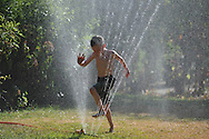 Mason Bagwell runs through a sprinkler to cool off  in Oxford, Miss. on Tuesday, July 2, 2012.