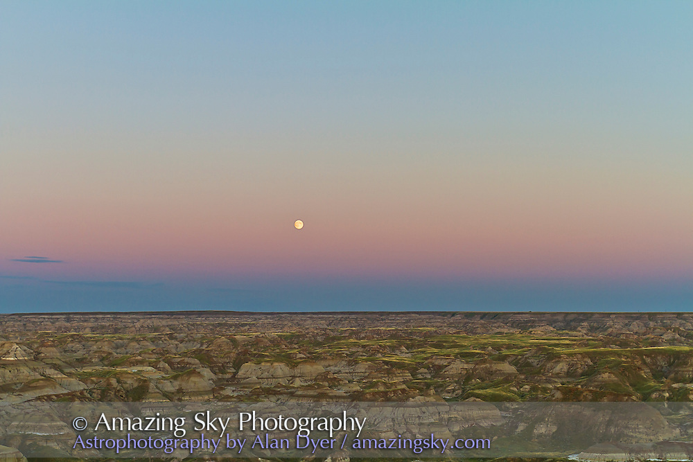 "Moonrise the day before Full Moon, over the badlands of Dinosaur Provincial Park, Alberta on August 23, 2010. Taken from the ""top of the hill"" viewpoint at the entrance to the Park. Taken with a Canon 7D and 16-35mm lens at 32mm and ISO 100. Exposure metered. Still is a frame from a 750-frame time-lapse sequence."
