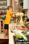 A young boy of five works alone in the kitchen with a cake mixer Model release available
