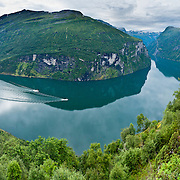 Geirangerfjorden (the Geiranger fjord) is a stunningly beautiful 15-kilometer (9.3-mile) long branch of Storfjord (Great Fjord, the fifth longest in Norway). Geirangerfjord is one of Norway's most visited tourist sites and has been listed as a UNESCO World Heritage Site since 2005. Take the car ferry for an impressive sightseeing trip between Geiranger and Hellesylt, in Stranda municipality, Sunnmøre region, Møre og Romsdal county, Norway. Panorama stitched from 10 overlapping photos.