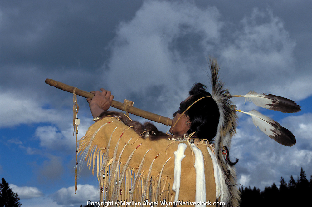 Nez Perce flute player, Levi Holt aka Black Beaver, plays an enchanting tune on a Native American cedar flute while dressed in traditional buckskin fringed shirt with ermine skins and a roach headdress with 2 eagle feathers