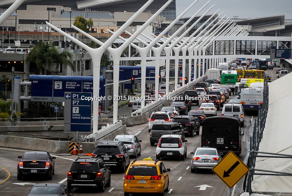 12月22日,在美国洛杉矶国际机场,汽车堵塞在车道上。根据南加州汽车俱乐部(Automobile Club of Southern California) 发表最新报告,在圣诞新年假期期间(12月23日至1月3日),全加州将创纪录有1230万民众出游50英里以上的目的地,其中南加州将佔760万民众。洛杉矶国际机场官员同时表示,他们亦预计有创纪录350万人次在假日期间使用机场往返国内国外,比去年同期增加7.9%,将使洛杉矶国际机场成为全美最繁忙的机场。新华社发 (赵汉荣摄)<br /> Traffic fills arrival and departure lanes at Los Angeles International Airport as people travel to Christmas and New Year holiday destinations on Tuesday, December 22, 2015 in Los Angeles, the United States. A record 12.3 million California residents -- 7.6 million of them from Southern California -- will travel 50 miles or more between Dec. 23 and Jan. 3, the Automobile Club of Southern California said. Los Angeles International Airport officials, meanwhile, said they expect<br /> a record 3.5 million passengers to pass through the airport during the holiday travel season, up 7.9 percent from last year. That would make LAX the nation's busiest over the holidays, officials said. (Xinhua/Zhao Hanrong)(Photo by Ringo Chiu/PHOTOFORMULA.com)<br /> <br /> Usage Notes: This content is intended for editorial use only. For other uses, additional clearances may be required.