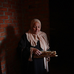 Cairo, Egpyt: Oum Hashem Rashad, 46,  takes bread downstairs from her home made, wood burning oven in Fayoume, Egypt December 5, 2005. She is a recipient of the telefood project by FAO which has enabled her to have a small garden on her roof. The extra food has  provided an extra income for her family and also fresh, pesticide free vegetables. (Photo Ami Vitale)