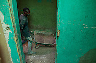 A man takes a wheelbarrow back inside a building to remove rubble on July 6, 2010 in Port-au-Prince, Haiti. Nearly all the cleanup is being done by hand.