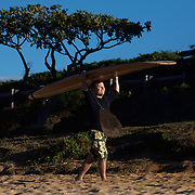 A surfer carries his board along Hookipa Beach, one of the best surfing and windsurfing areas in the Hawaiian Islands.  Located on the north shore of Maui, many world championship contests are held here.