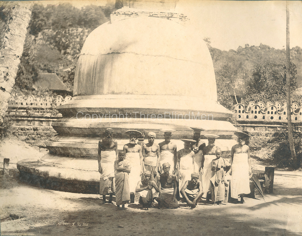 Kandy. A group of men and young monks in front of a stupa or dagoba.<br />