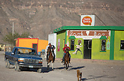 Locals ride down main street in Boquillas del Carmen on May 14, 2014. The town has two restaurants, one bar, and a small store. Residents make most of their income from tourists that visit in the cooler months.