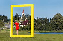 Woman standing in National Geographic yellow window in Rõuge, Estonia. View through frame.