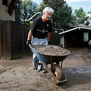 BOULDER, CO - SEPTEMBER 13: Jeff Kandyba of Boulder, Colorado removes a wheelbarrow full of silt from his driveway as he tries to clean up after heavy rains for the better part of week fueled widespread flooding in Boulder, Co. on September 13, 2013. (Photo by Marc Piscotty/ © 2013)